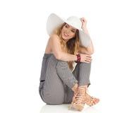 Schönheit im Overall, in Sun-Hut und in den hohen Absätzen sitzt auf Boden und schaut weg Stockbild