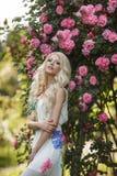 Schönheit im Park nahe den blühenden Rosen Bushs Lizenzfreie Stockfotografie