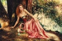 Schönheit im roten Kleid, das auf einer Natur sitzt Stockbild