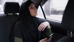 Schönheit im schwarzen hijab, das auf dem Rücksitze im Auto sitzt und neugierig auf der Straße während die Straße schaut stock footage