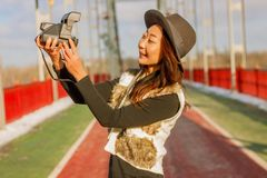 Schönheit im schwarzen Hut macht ein polaroidselfie auf einer Brücke im Winter in Europa lizenzfreie stockfotografie