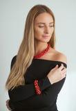 Schönheit im schwarzen Kleid mit roter Halskette und Armband Stockbilder