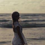 Schönheit im Sommerkleid, das im Ozean auf Sonnenuntergang evei steht Stockfotografie