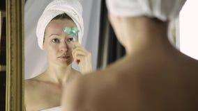 Schönheit im Tuch, das kosmetische Verfahren im Haus tut Gesichtsmassage mit Massager stock video footage