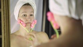 Schönheit im Tuch, das kosmetische Verfahren im Haus tut Gesichtsmassage mit Massager stock footage