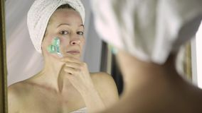 Schönheit im Tuch, das kosmetische Verfahren im Haus tut Gesichtsmassage mit Massager stock video