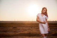 Schönheit im weißen Kleid, das auf dem Sonnenuntergang mit sexy Blick aufwirft stockbilder