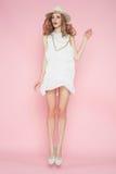 Schönheit im weißen Kleid, das auf rosa Hintergrund im Hut aufwirft Stockbild