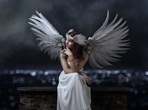 Schönheit im weißen Kleid mit Engel beflügelt auf einen Hintergrund Lizenzfreie Stockbilder