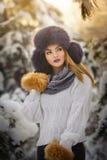 Schönheit im weißen Pullover mit übergroßer Pelzmütze die Winterlandschaft im Waldblonden Mädchen genießend, das im Winter aufwir Stockfoto