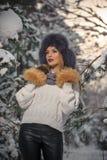Schönheit im weißen Pullover mit übergroßer Pelzmütze die Winterlandschaft Waldin der blonden Mädchenaufstellung genießend Lizenzfreie Stockbilder
