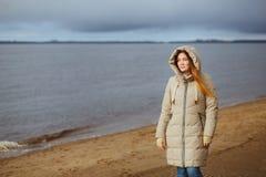 Schönheit im Winter kleidet das Bereitstehen des Flusses und das Schauen zum Wintersonnenuntergang Saisonal, Mode und Verhältnis Stockfotos