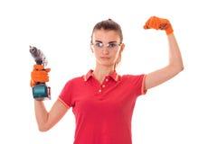 Schönheit lässt junges Brunette-Erbauermädchen in der Uniform und in den Gläsern Erneuerung mit die Hände herein bohren, die auf  stockbild