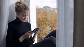 Schönheit liest das eBook, das auf Fensterbrett sitzt stock footage