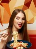 Schönheit mit ausdrucksvoll geöffnetem Mund Fettuccine essend stockfotos