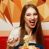 Schönheit mit ausdrucksvoll geöffnetem Mund Fettuccine essend stockbilder
