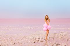Schönheit mit baloons auf rosa Salzsee lizenzfreie stockfotos