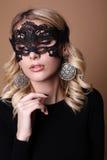 Schönheit mit blondem gelocktes Haar- und Abendmake-up, mit Spitzemaske auf Gesicht Lizenzfreie Stockbilder