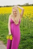 Schönheit mit Blumenblumenstrauß im Rapsfeld Lizenzfreies Stockbild