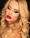 Schönheit mit dem blonden gelockten Haar und hellen dem Make-up, die i aufwirft stockbild