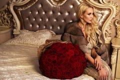 Schönheit mit dem blonden Haar in der luxuriösen Kleidung, die mit aufwirft Lizenzfreie Stockfotografie