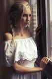 Schönheit mit dem blonden Haar träumend neben einem Fenster Lizenzfreie Stockbilder