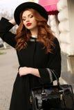 Schönheit mit dem dunklen gelockten Haar und reizend Lächeln, trägt elegante Kleidung Lizenzfreie Stockfotografie