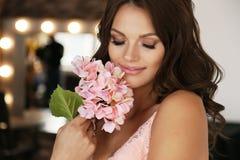 Schönheit mit dem dunklen Haar, das mit Blumen aufwirft stockbild