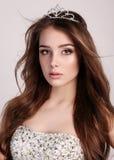 Schönheit mit dem dunklen Haar trägt elegantes Kleid und kostbare Krone Lizenzfreie Stockfotografie
