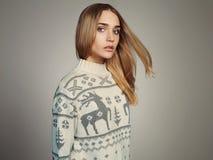 Schönheit mit dem Fliegenhaar im Winterpullover Blondes Mädchen der Schönheit Stockfotografie