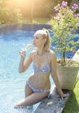 Schönheit mit dem langen angemessenen Haar mit einer dünnen Zahl in einer Bikinibadebekleidung mit einem Glas Sekt im Pool mit Br Lizenzfreies Stockfoto