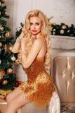 Schönheit mit dem langen blonden Haar im eleganten Kleid, das nahe verziertem Weihnachtsbaum aufwirft lizenzfreies stockfoto