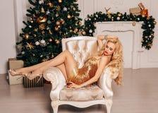 Schönheit mit dem langen blonden Haar im eleganten Kleid, das nahe verziertem Weihnachtsbaum aufwirft stockfotografie