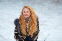 Schönheit mit dem langen roten Haar auf einem schneebedeckten Hintergrund Stockfoto
