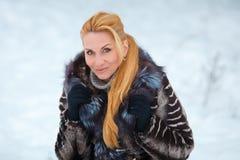 Schönheit mit dem langen roten Haar auf einem schneebedeckten Hintergrund Stockfotografie