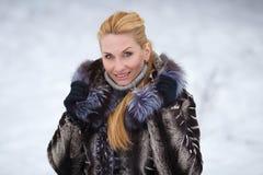 Schönheit mit dem langen roten Haar auf einem schneebedeckten Hintergrund Stockbild