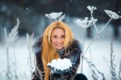 Schönheit mit dem langen roten Haar auf einem schneebedeckten Kuh-Pastinak Lizenzfreies Stockfoto