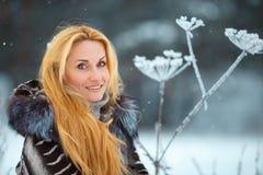 Schönheit mit dem langen roten Haar auf einem schneebedeckten Kuh-Pastinak Stockbild
