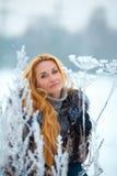 Schönheit mit dem langen roten Haar auf einem schneebedeckten Kuh-Pastinak Stockfotos