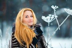 Schönheit mit dem langen roten Haar auf einem schneebedeckten Kuh-Pastinak Stockfotografie