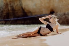 Schönheit mit dem perfekten Körper, der sich auf dem Strand hinlegt, genießen frisches Ozeanwasser lizenzfreie stockbilder