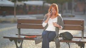 Schönheit mit dem roten Haar sprechend am Handy, der auf einer Bank in der Straße mit Gebäuden in sitzt stock video footage