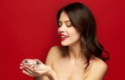 Schönheit mit dem roten Lippenstift, der Diamanten hält Lizenzfreie Stockfotos