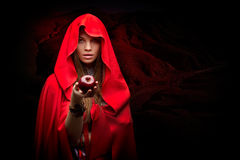 Schönheit mit dem roten Mantel, der Apfel hält Lizenzfreie Stockfotografie
