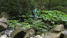 Schönheit mit dem Rucksack wandern, der Foto durch Smartphone auf Gebirgsfluss mit großen Flusssteinen und grünem Moos herein mac stock video footage