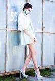 Schönheit mit den langen Beinen in der weißen Kleider-, Pelz- und Absatzaufstellung im Freien Stockbilder