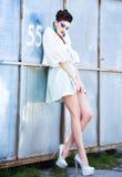 Schönheit mit den langen Beinen in der weißen Kleider-, Pelz- und Absatzaufstellung im Freien Stockfoto