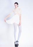 Schönheit mit den langen Beinen in der weißen Kleider- und der hohen Absätzeaufstellung Stockfoto