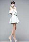 Schönheit mit den langen Beinen im weißen Kleid, im Pelz und in den hohen Absätzen Lizenzfreies Stockbild