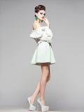Schönheit mit den langen Beinen im weißen Kleid, im Pelz und in den hohen Absätzen Stockfotos